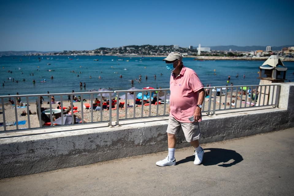 A man wearing a face mask walks along the ″Pointe Rouge″ beach Marseille France