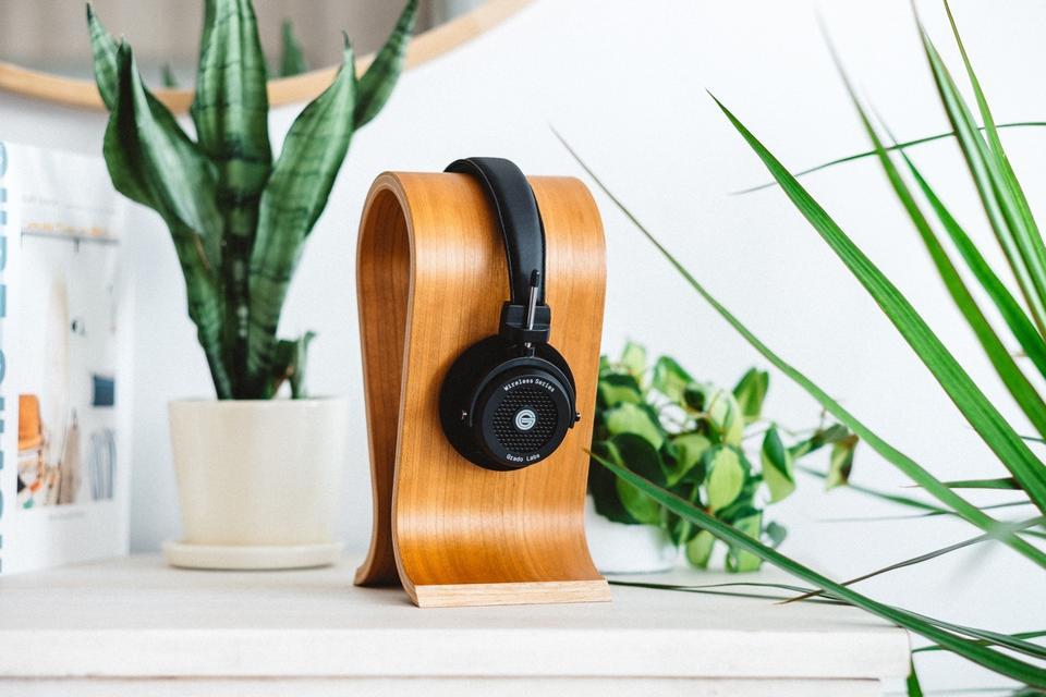 A pair of Grado GW100 headphones in a wooden headphone stand
