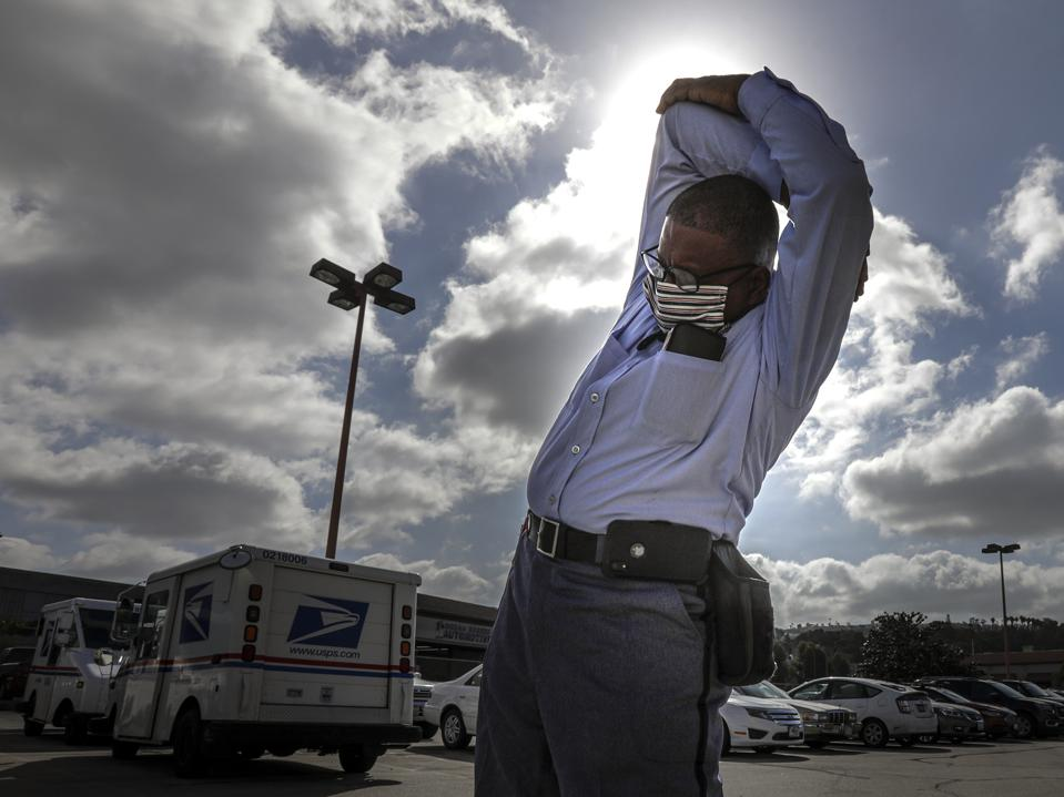 USPS Postal Workers stretching with a mask on before work. mail truck in the background.