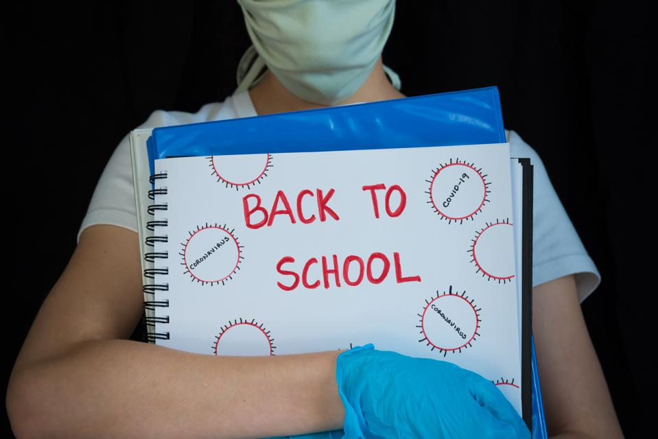 Close-up of student wearing face mask and surgical gloves, holding school books with Back to School written on cover