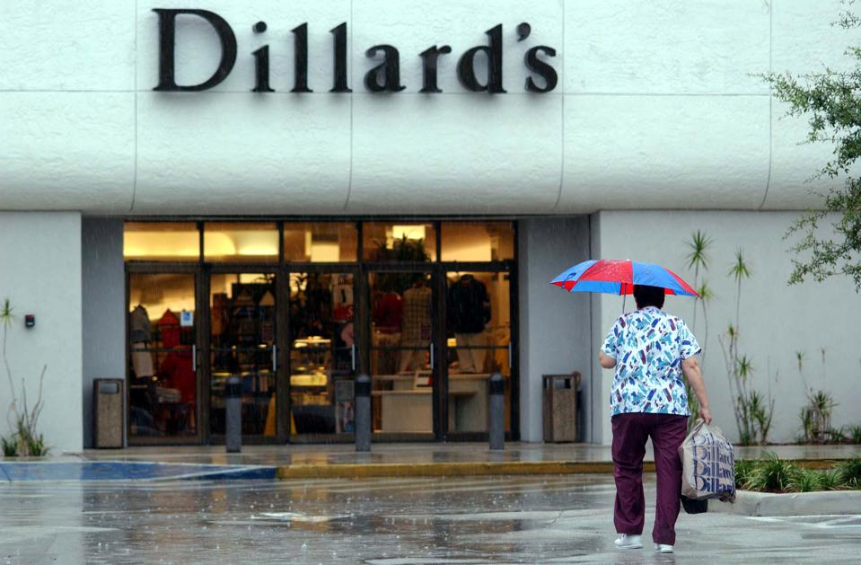 A shopper totes a Dillard's shopping bag as she heads into the store through a driving rain at the Broward Mall in Plantation, Florida, on Wednesday, August 20, 2003. Dillard's Inc. had a second-quarter loss of $50.4 million as sales fell after the 65-year-old department-store company reduced prices to try to keep shoppers from going to discounters and retailers such as Kohl's Corp.Shares of Dillard's declined as much as 13 percent. Photographer: Richard Sheinwald/Bloomberg News