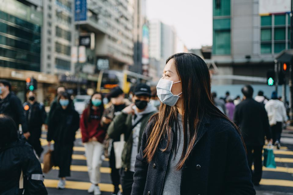 Asian woman with protective face mask crossing road in busy downtown city street against crowd of pedestrians and highrise urban buildings