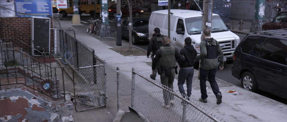 Immigration and Customs Enforcement (ICE) agents escort an unauthorized immigration to detention in the Netflix film Immigration Nation.