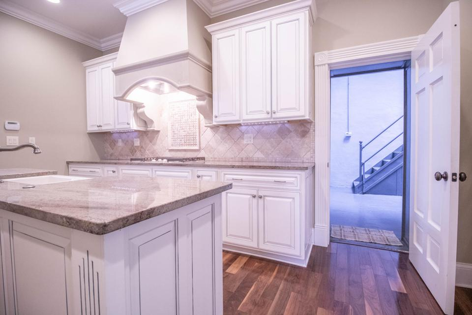 I white and gray kitchen with a center island opening up to a hallway with a staircase.