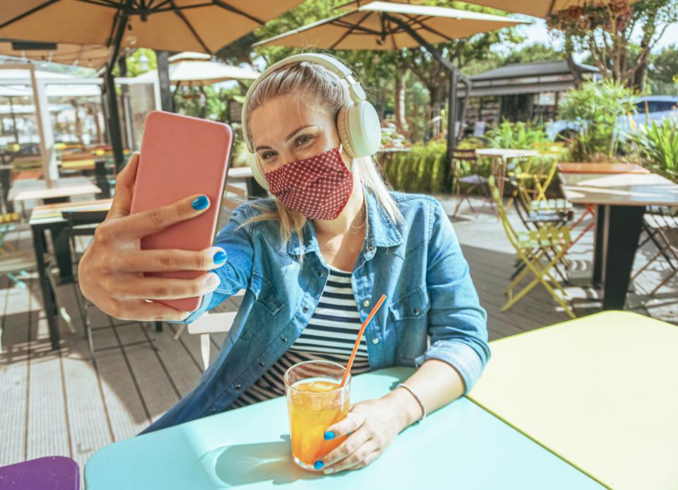 Girl in bar takeing a selfie with a smartphone with her face mask on as a protection for coronavirus time - Teenager chilling outside and enjoying a cold drink - Lifestyle of covid-19
