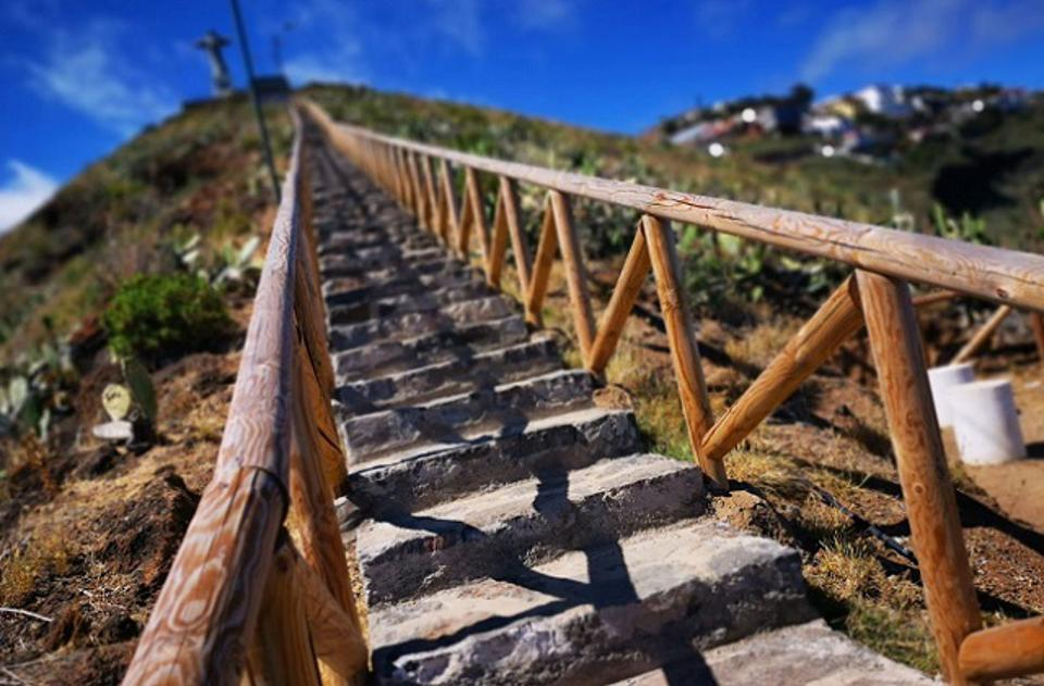 A stairway leading upwards on a mountain trail in the sunshine.
