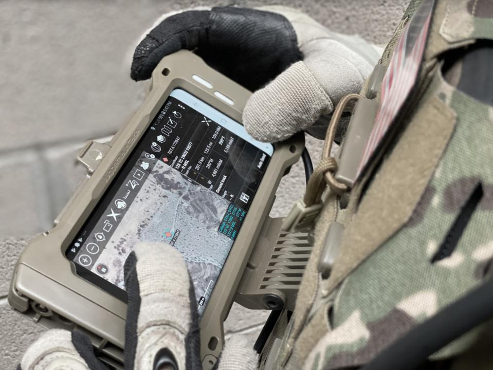 A military Sasmung S20 TE smartphone in the hands of a soldier
