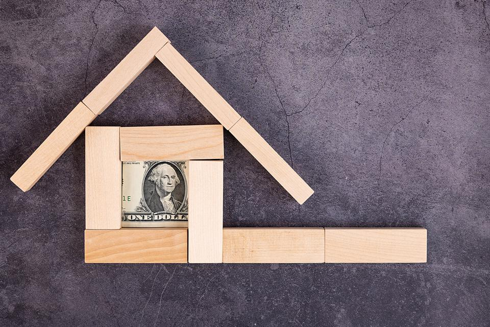 A dollar bill folded between wooden blocks arranged in the shape of a house.