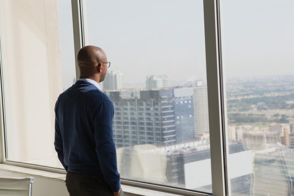 African businessman admiring city through window