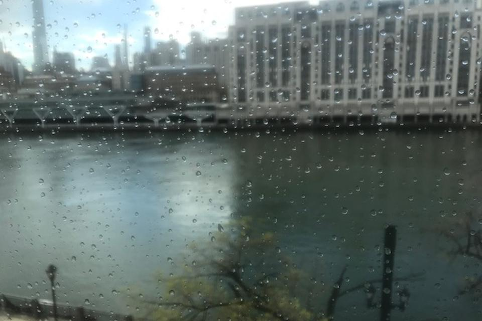 View of the East River and behind it NY Hospital through a class screen covered with rain drops. The left half of the East River mirrors blue sky and clouds, the right part is dark and mirrors the hospital.