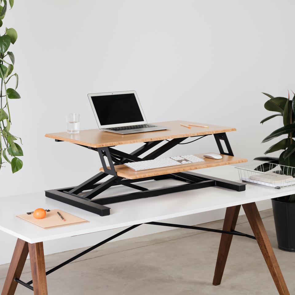 A desk riser makes office work more ergonomic and healthy with sit/stand flexibility.