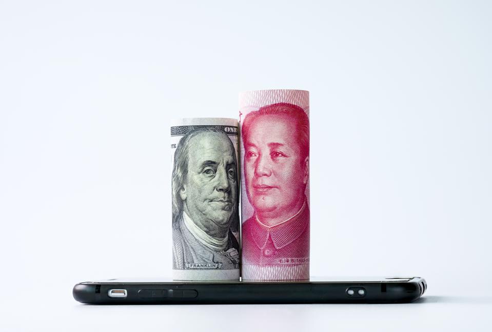 Closeup US dollar and China Yuan banknote on mobile phone