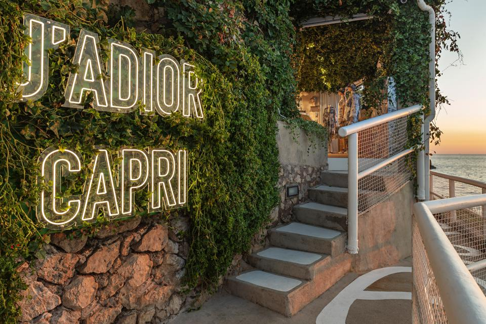Atop the cliffs of Capri, a neon sign reading J'ADIOR CAPRI on a vine-covered rock wall marks the entrance to seasonal Dior shop located there.