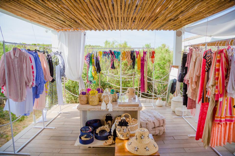 Interior image of an open air summer beachwear pop-up  set amongst trees with wood deck floor and bamboo thatched ceiling.