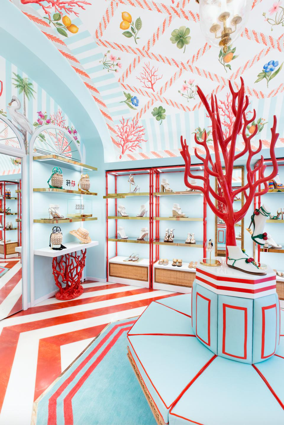 Inside of Aquazurra shoe boutique in Capri with a turquoise and orange color scheme with coral accents and traditional motif wallcovering