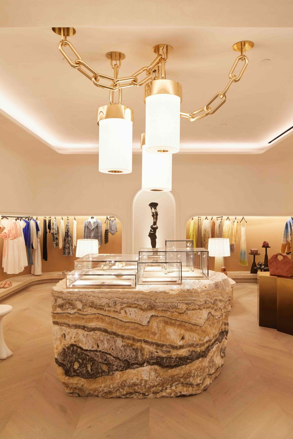 Interior of upscale boutique The Webster at Rosewood Miramar Beach resort featuring wood floors, recessed lighting clothing racks, and massive rock display table placed underneath three-lantern lighting fixtures adorned with a heavy chain.