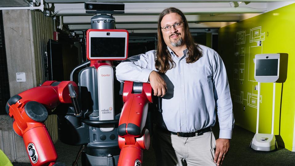 Researcher Peter Haas standing next to robot