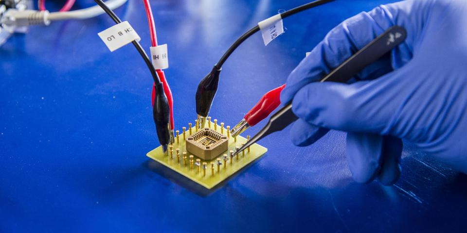 A gloved hand in a lab probing a microchip