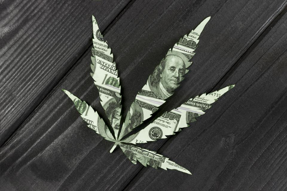 A cannabis leaf made of dollar bills on wooden background