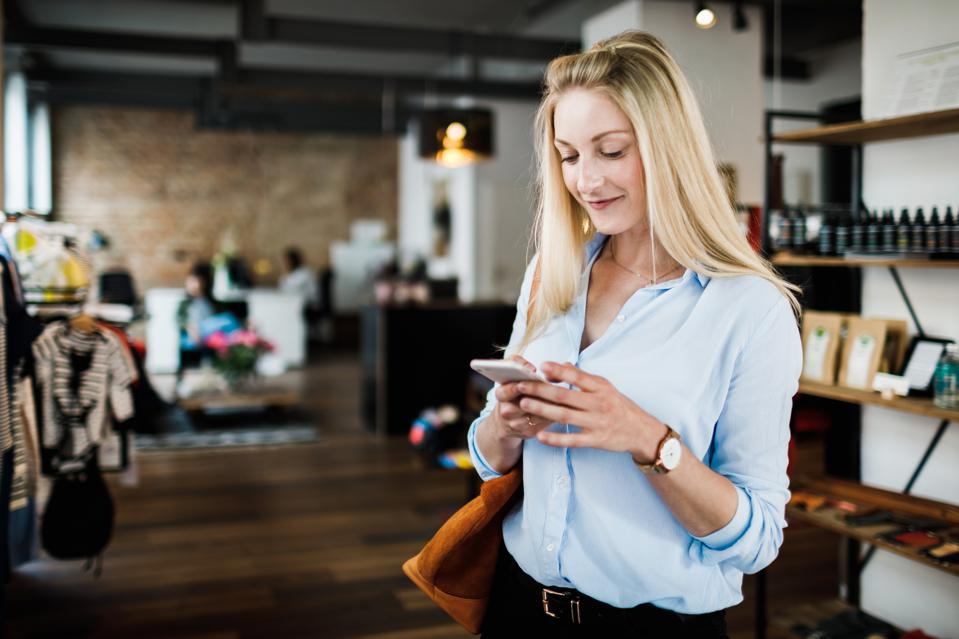 Young Woman Using Smartphone While Clothes Shopping