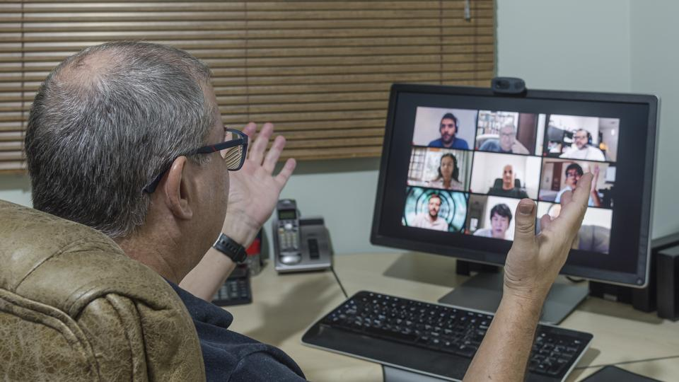 Adult man on video conference call viewing computer monitor with several faces