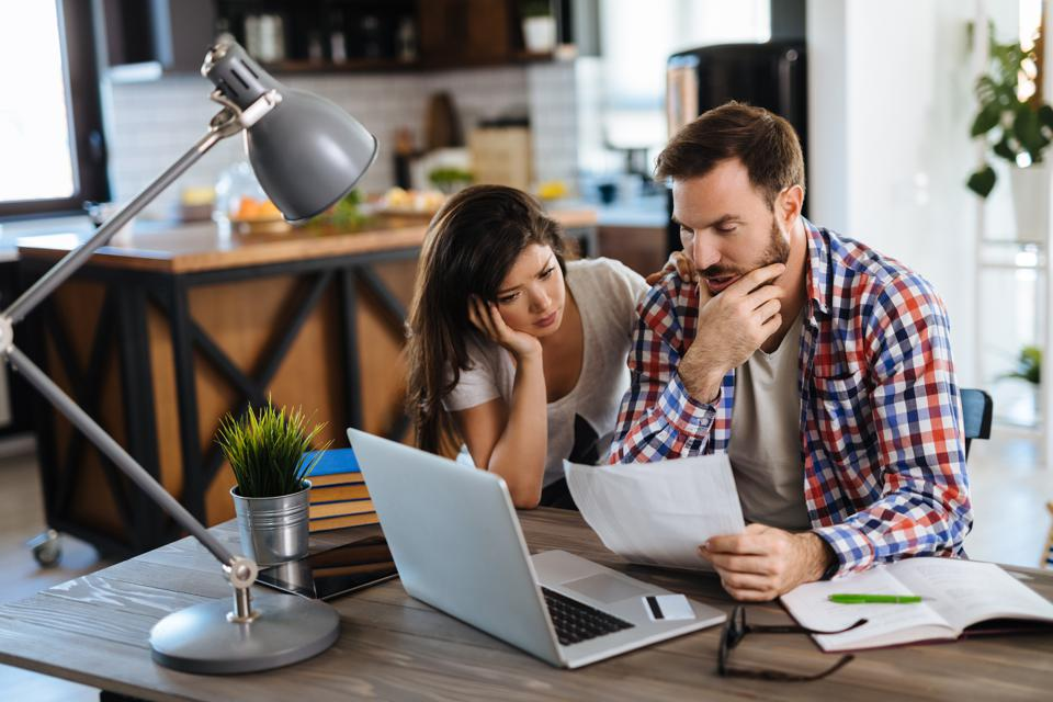 Frustrated couple checking bills