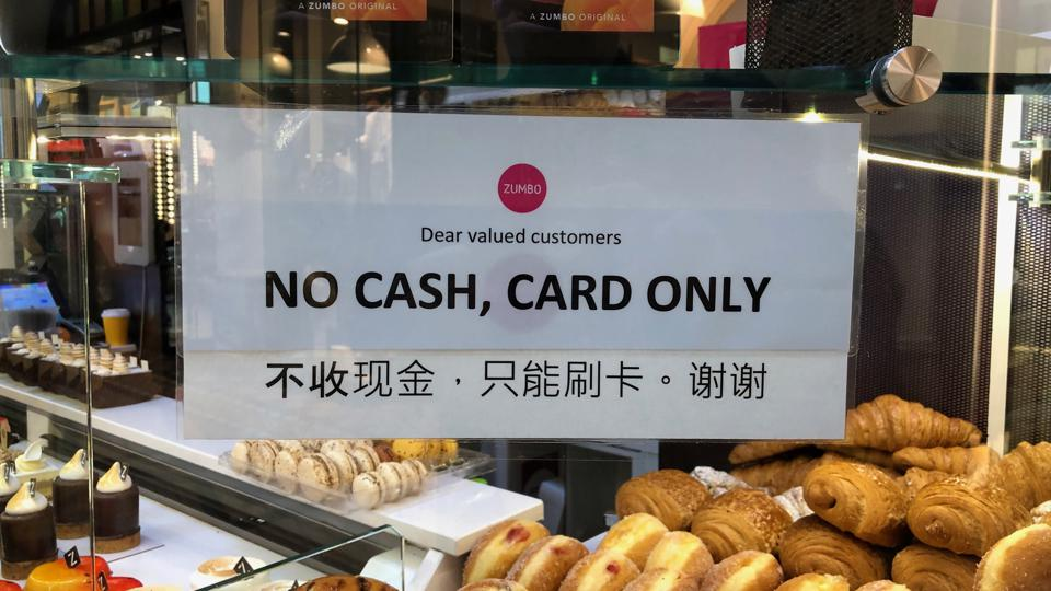 A sign in a shop window saying ″no cash, card only″.