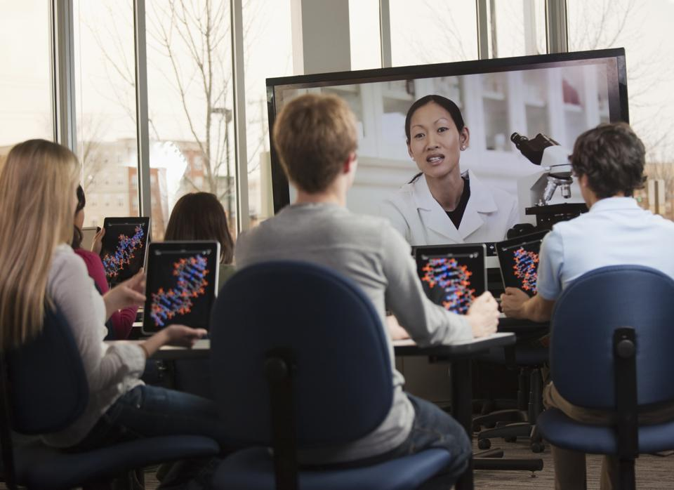Students with digital tablets watching instructor on monitor