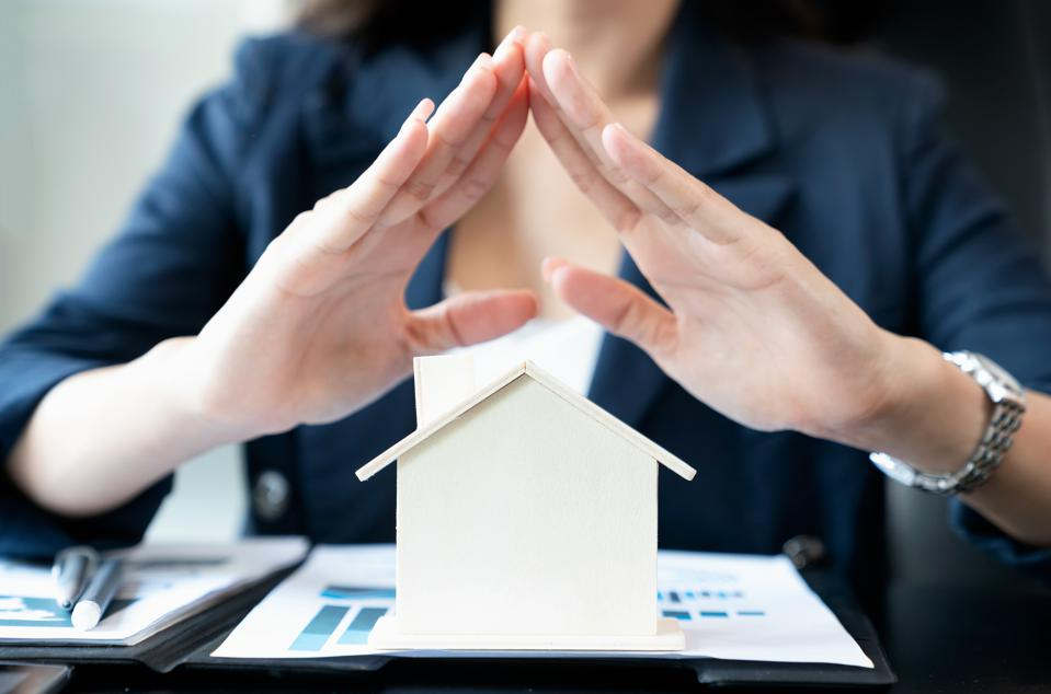 Hands of businesswoman covering the wood house. Property insurance and security concept. -