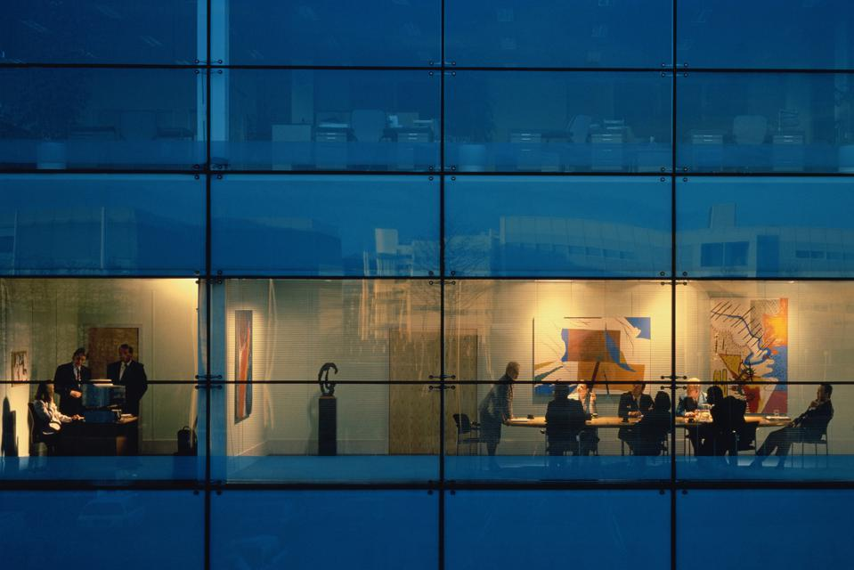 Executives in conference room, view through window