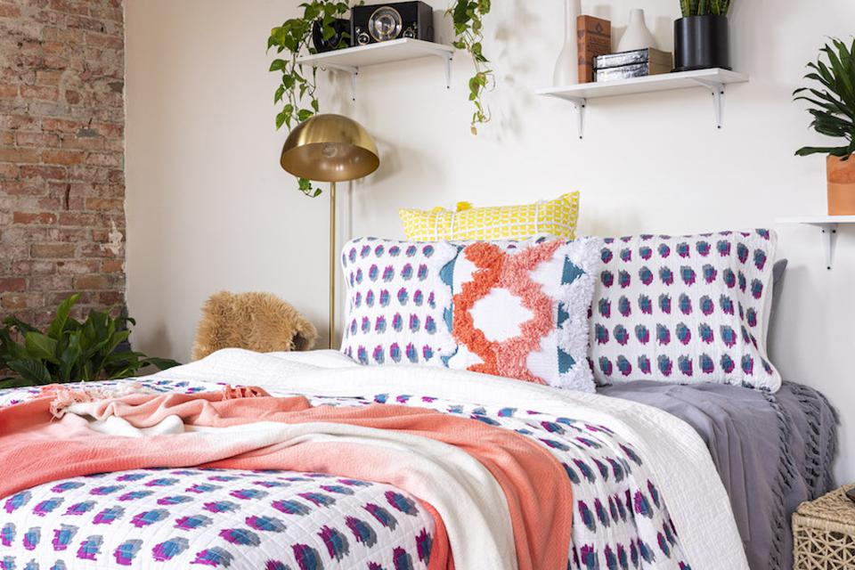 Patterned bedding on a bed with a throw and pillows.