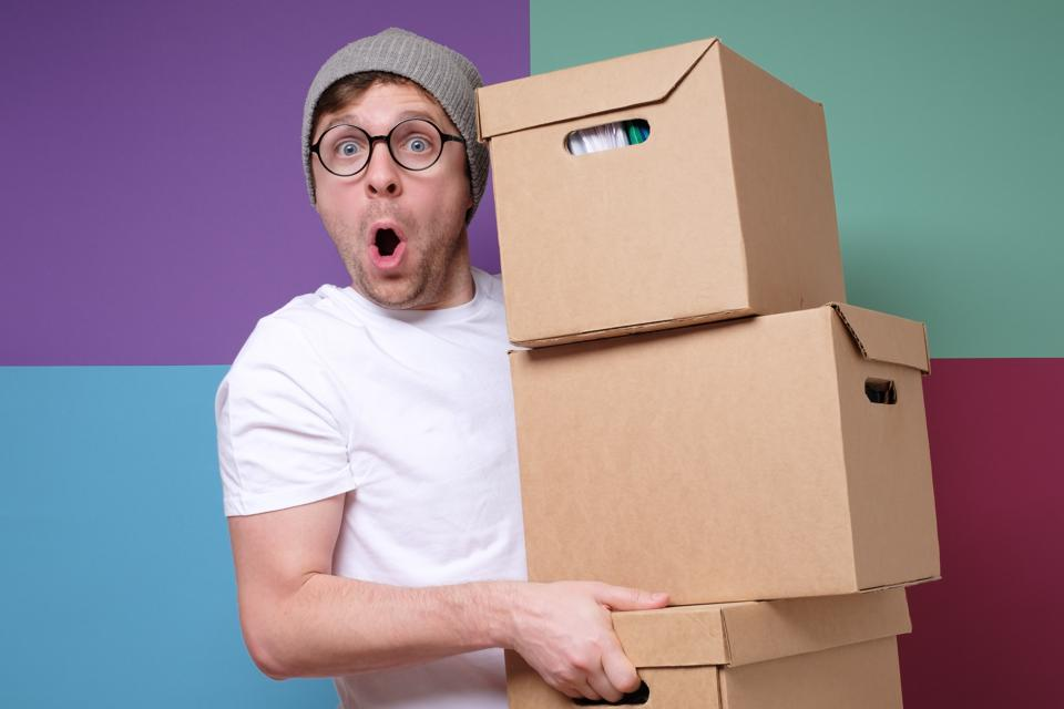 Young hipster man in hat and glasses carrying paper boxes isolated on colored background