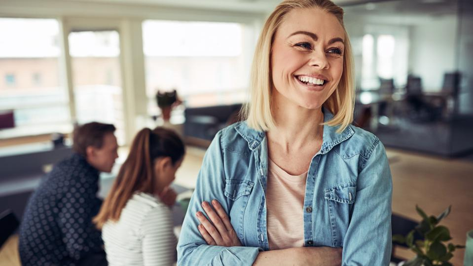 Smiling young businesswoman laughing with coworkers in the background