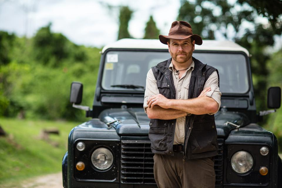 Josh Gates with a wide-brimmed hat standing in front of a vintage Land Cruiser in the jungle.