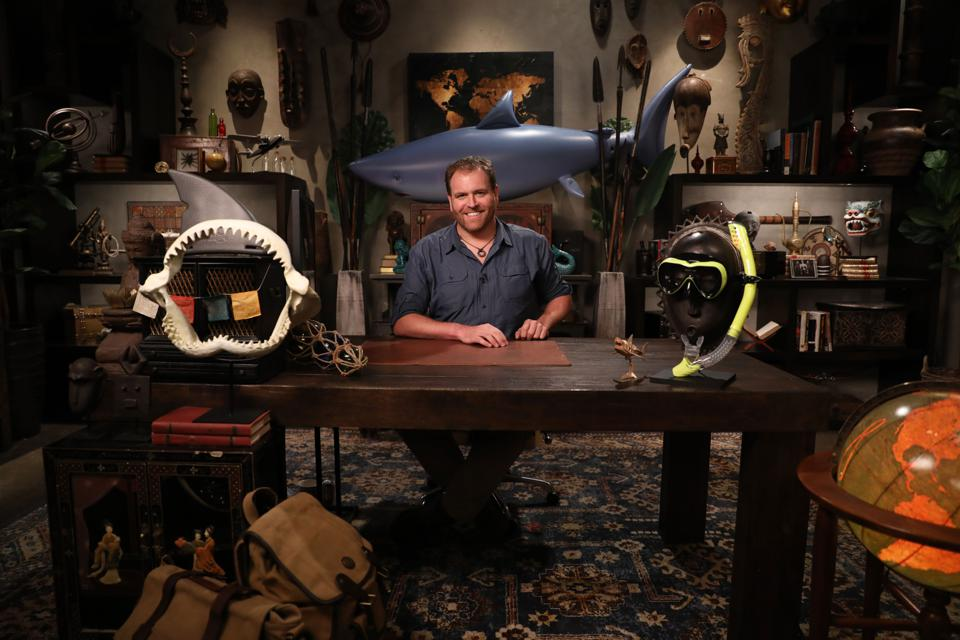 Josh Gates at a large wooden desk in a room filled with artifacts from around the globe.
