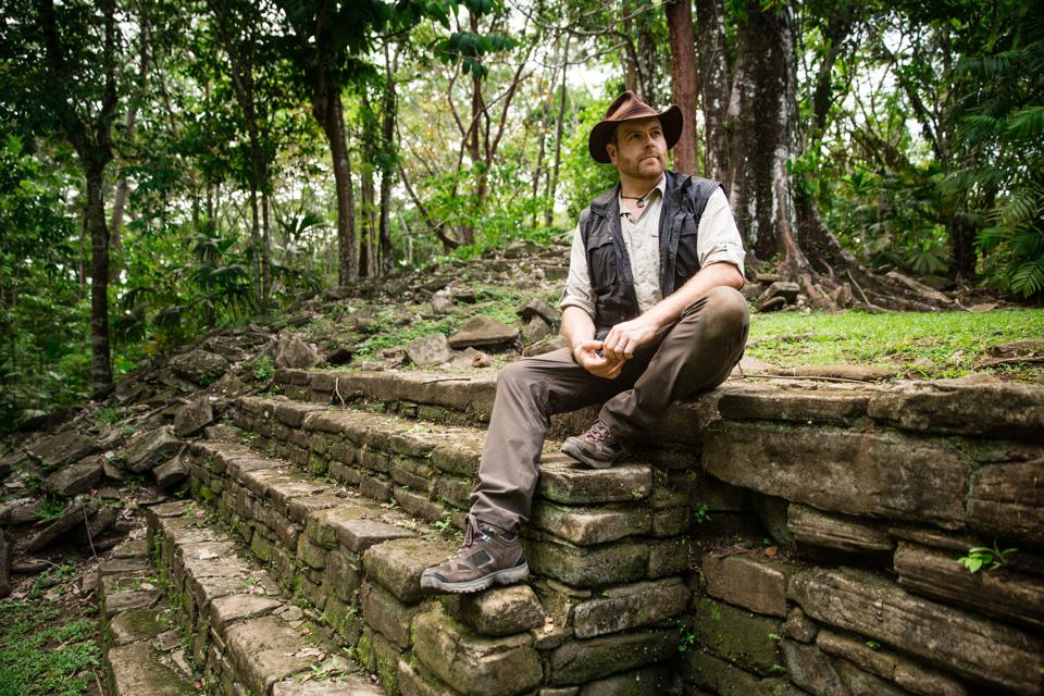 An explorer sits atop the ruins of a Mayan pyramid in the green jungles of Belize.