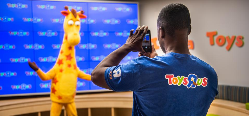An employee takes a photograph of a person dressed as Geoffrey the Giraffe at a Toys R Us Inc. store in Paramus, New Jersey, U.S., on Tuesday, Nov. 26, 2019.