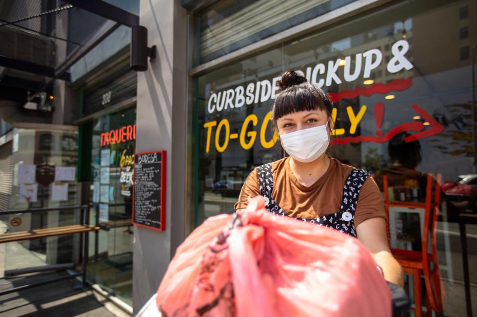 Masked Restauranteur During Covid-19 Lockdown Holding Out Bagged Order to Camera