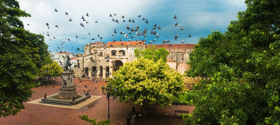 Doves flying over main square with Columbus statue, Santo Domingo, Dominican Republic.