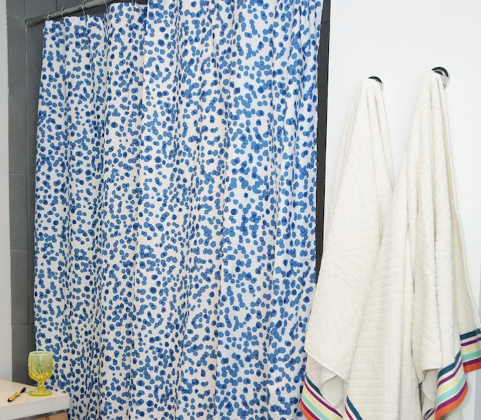 A bathroom with a blue dot shower curtain and white towels with multi-colored stripes.