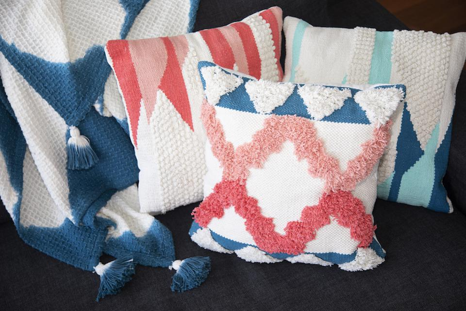 Blue and white ombre throw and multi-colored pillows.