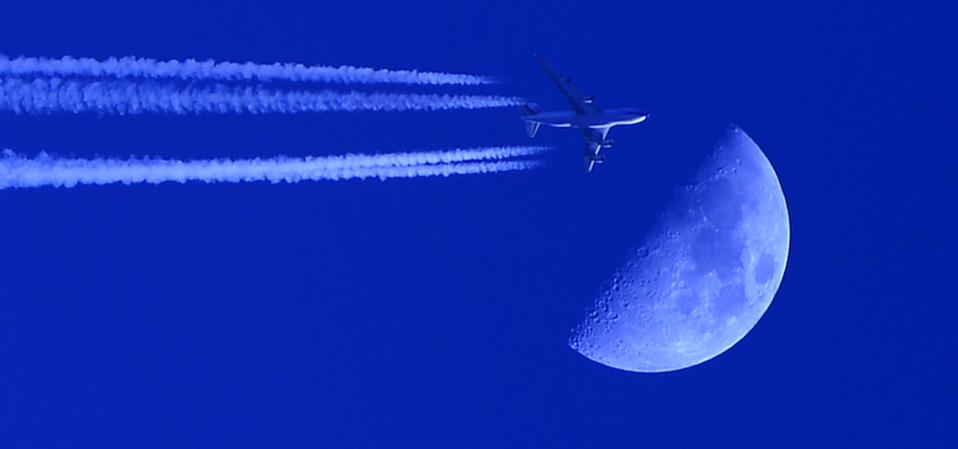 A plane passes by the first quarter moon in the sky (Photo by Ozkan Bilgin/Anadolu Agency/Getty Images)