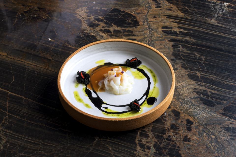 A dish of calamari with black garlic at Cinc Sentits restaurant in Barcelona.