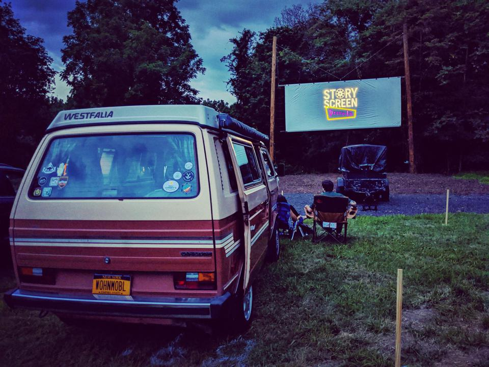 A van parked at an outdoor movie theater.