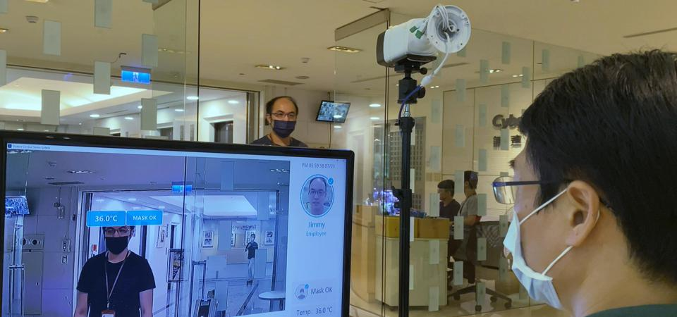 An employee uses a camera and monitor connected to the CyberLink FaceMe Health software to check visitors for mask compliance and body temperature.