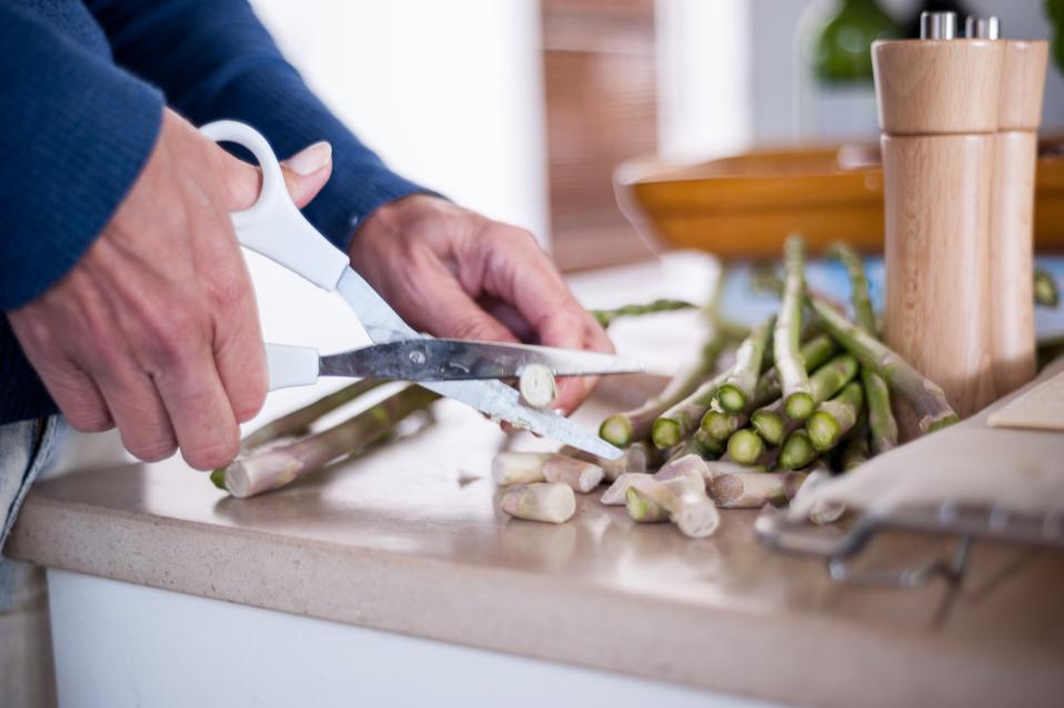 Woman using scissors to cut asparagus.