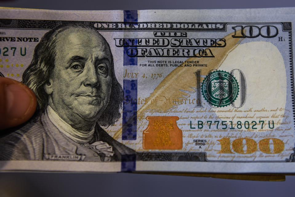 In this photo illustration 100 US dollar banknotes seen...