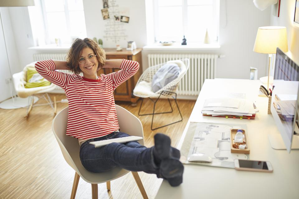 Portrait of smiling mature woman relaxing on armchair at home office