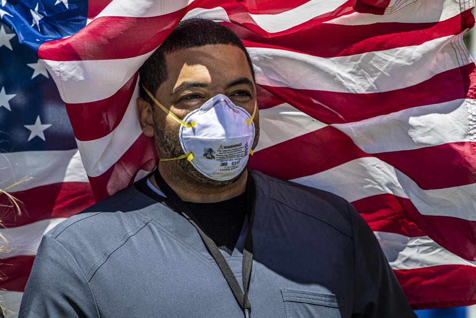 Nurse poses in front of American flag during salute to healthcare workers on Long Island