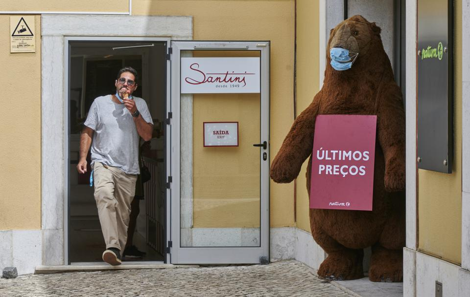A man leaves an ice cream parlour next to a giant toy bear wearing a Covid mask in Portugal